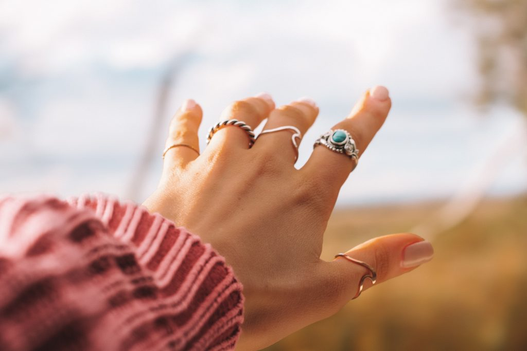 A hand with a horizontal silver ring stack